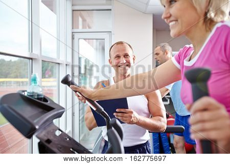 Mature woman working out on cross trainer and her personal trainer