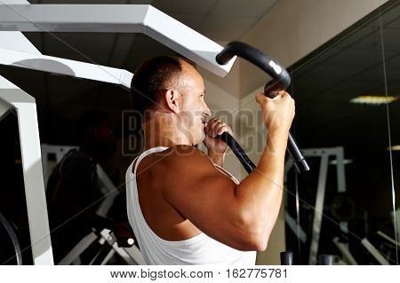 Mature muscular man doing chin ups in gym