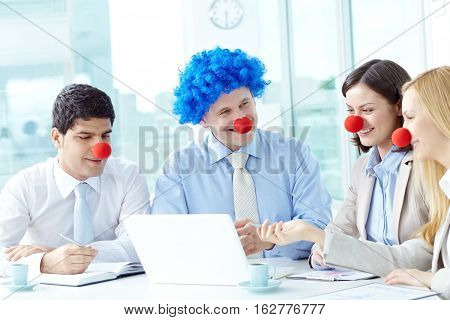 Business people wearing clown noses communicating at meeting