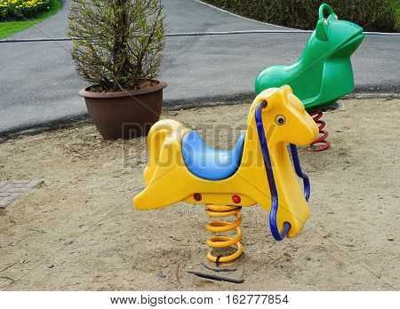 Old colorful seesaw in sand public playground