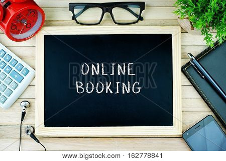 Top view of earphone, calculator, alarm clock, spectacle, notebook, pen, smartphone and chalkboard written with ONLINE BOOKING.