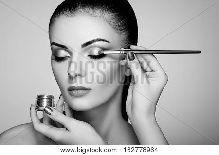 Makeup artist applies eye shadow. Beautiful woman face. Perfect makeup. Makeup detail. Beauty girl with perfect skin. Nails and manicure. Black and White