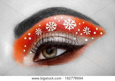 Eye girl makeover snowflakes. Winter christmas makeup. Beauty fashion. Eyelashes. Cosmetic Eyeshadow. Makeup detail. Creative woman holiday make-up
