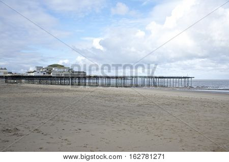 Colwyn Bay pier, Victorian architecture with sand and blue sky with clouds