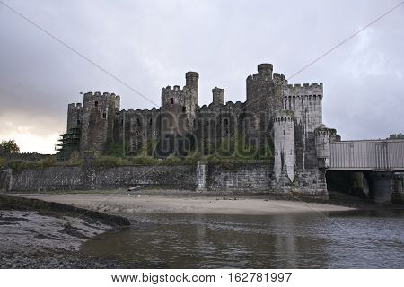 Conwy Castle south side showing stormy weather, sand bank, and river conwy