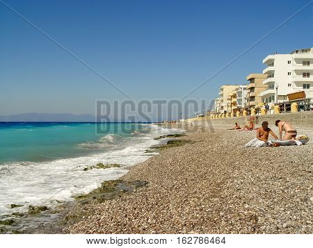 Tourists Enjoying And Swimming The Pebble Beach In Rhodes