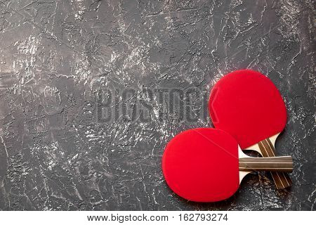 Red racket for ping pong ball on gray background top view