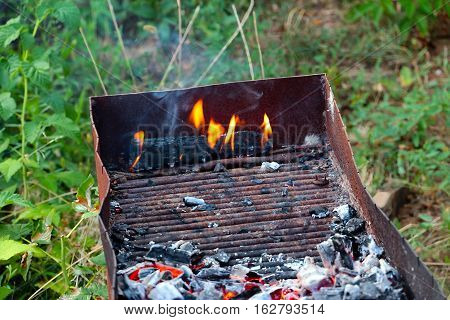 bright flames and hot pieces of natural charcoal in the brazier