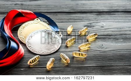 Concept of doping in sport - deprivation medals close up on dark wooden background