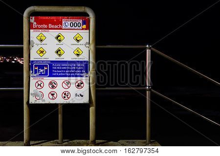 Sydney, Australia - May 28, 2016: Safety warning signage at Bronte Beach, Sydney, New South Wales, Australia. This signboard is weathered and contains an assortment of safety icons. It is located at a stairway leading directly to the beach.