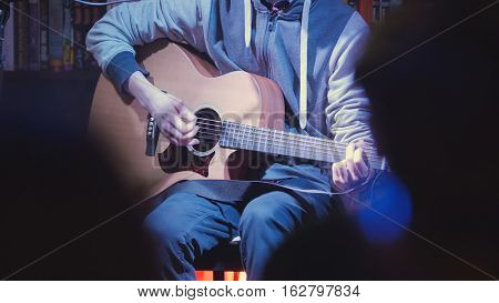 Close up view of guitarist plays acoustic guitar in night club, telephoto