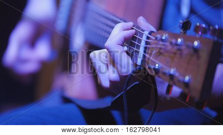 Musician in night club guitarist plays acoustic guitar, extremely close up, telephoto
