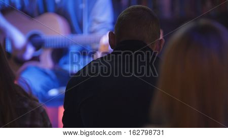 Spectators looks at guitarist plays acoustic guitar in night club, telephoto