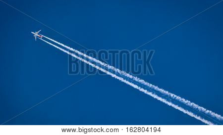 The plane is flying against the blue sky. The plane has a vapor trail.