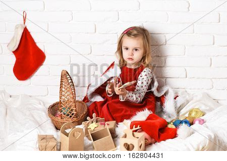 young cute little blonde girl in christmas coat and red dress sitting around xmas basket or new year boxes gifts and colorful balls with decorative stocking or boot on white brick wall background