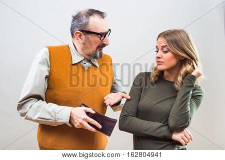 Nerdy man is showing to his beautiful wife that he doesn't have any more money and she is disappointed.