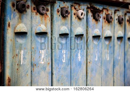 Old metal rusted and numbered mailboxes. Painted blue. Paint partly peeled off. Focus on locker number 3.