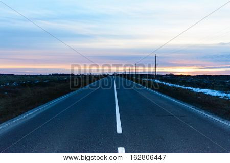 Sunset over the road covered with asphalt that goes away. On either side of an empty field. Cold season.