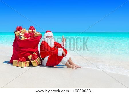 Santa Claus relax thumbs up gesturing at ocean tropical sandy beach with Christmas sack full of wrapped gift boxes. Happy New Year travel destinations for tropical vacations concept