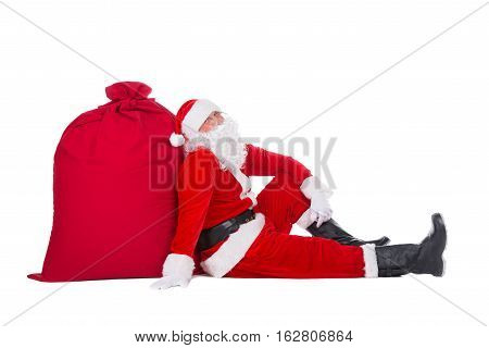 Santa Claus have rest sitting near big Christmas sack full of presents gifts and surprises at New Year or xmas holidays isolated on white background