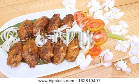 Marinated chicken wings fried and vegetable on wood has decorate are onions tomato on the banana leaf in plate and background is canna flower.