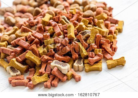 dry dog food in bulk on wooden background close up.