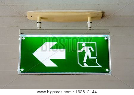 old Green fire exit sign at hotel.