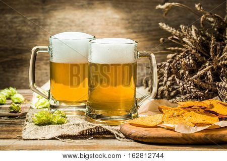 Two beer mugs with hops and chips on boards on linen cloth on wooden table