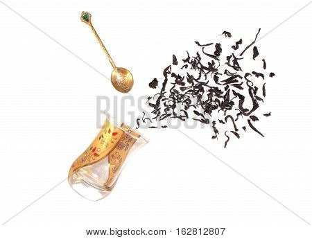 Turkish glass of tea with spoon and black tea leaves isolated on a white background. The concept of the tea party. Flat lay.