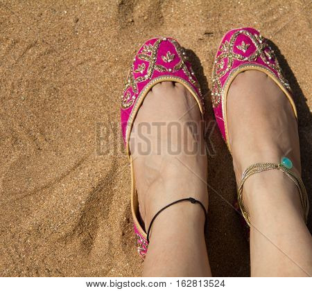 A lady wearing a pair of pink traditional Indian women's shoes (jutis) at the Anjuna beach in north Goa, India