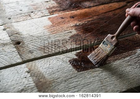 Painter holding a paintbrush over wooden surface protecting wood for exterior influences and weathering. Do-it-yourself concept.