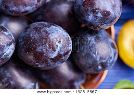 Fresh juicy raw plums in a wicker basket at a blue wooden background. Top view. Concept photo. Universe in one plum. Close view