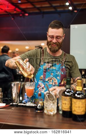 KIEV, UKRAINE - 30 OCTOBER, 2016: Barman festival. Handsome bearded hipster barman with long beard and mustache with funny face holding shaker and making alcoholic cocktail
