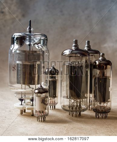 vertical composition of vacuum tubes on kraft paper in dual tone. vintage electronic background