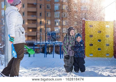 Mother and two son enjoying beautiful winter day outdoors kisd under snow trowing