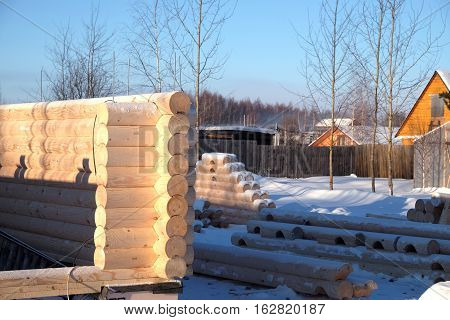 Construction of rural house from heavy logs in the village in winter season in clear sunny day. Horizontal photo