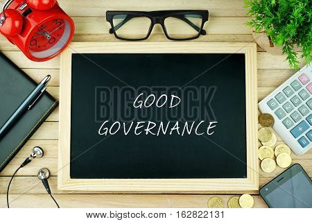 Top view of earphone, notebook, pen, alarm clock, spectacle, small green tree, calculator, coins, smartphone and black chalkboard written with GOOD GOVERNANCE inscription on wooden table.