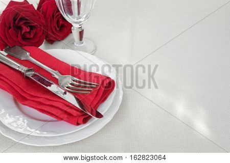 Beautiful decorated table with white plates rose flowers cutlery and wine glass on tablecloths with space for text