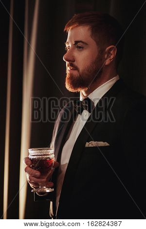 Young ginger bearded man holding a vintage glass with red wine against the light, black on background. view profile.