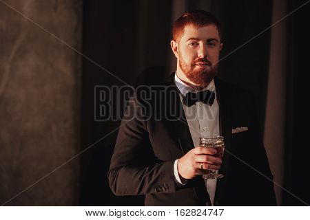 Young ginger bearded man holding a vintage glass with red wine against the light, black on background. look at the camera.