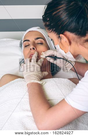 Young pretty woman getting rf lifting treatment on clinical center. Medicine, healthcare and beauty concept. poster