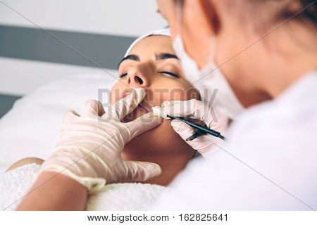 Close up of young pretty woman getting rf lifting treatment on clinical center. Medicine, healthcare and beauty concept. poster