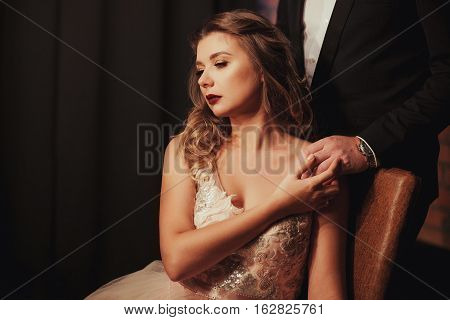 romantic Woman in pink bridal dress sitting on brown armchair. the bride holding the groom's hand. Indoor, interior, studio.