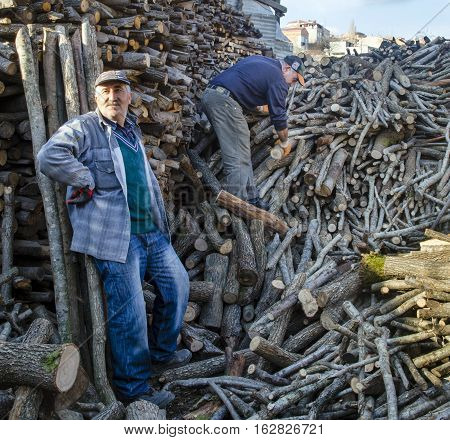 Istanbul Turkey - January 19 2014: Firewood for oven and stove heat source. Wood processing industry tree trunks piled up. There are people working on the firewood stacked in the photo.