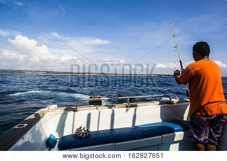 Bali Indonesia - 23 September 2016: Man preparing a hook and bait for a fishing pole on a small sport fishing vessel off the coast of Nusa Dua in Bali Indonesia