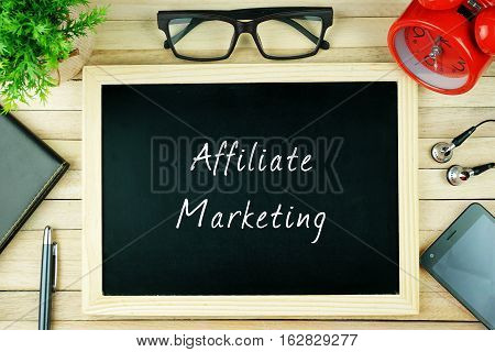 Top view of pen, diary, plant, eye glasses, alarm clock, smartphone, earphone and chalkboard written with AFFILIATE MARKETING on wooden background. Business Concept.