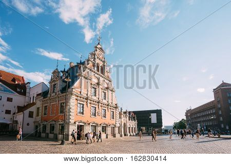 Riga, Latvia. Side View Of The Schwabe House At Town Hall Square, Ancient Historical Landmark And Popular Touristic Showplace With Walking People In Summer Sunny Day Under Blue Sky