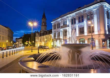 Vilnius, Lithuania - July 8, 2016: Gray Marble Fountain With Water Jets On Illuminated Rotuses Square. Steeple Of St. Nicholas Church Behind On Summer Evening Blue Sky.
