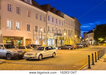 Vilnius, Lithuania - July 8, 2016: The Motionless Silver Mercedes Benz Taxi Car Among Parked Automobiles On Deserted Rotuses Square In Evening Illumination Under Summer Blue Sky.