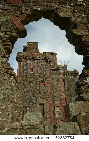 A view of Balvaird castle through a hole in a wall